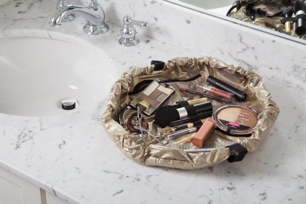 A gold Lay-N-Go Cosmo bag is seen laid out on a bathroom counter filled with cosmetics