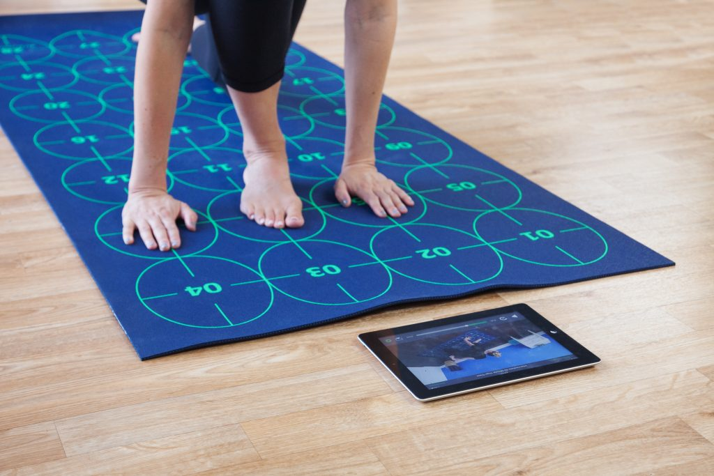 A person is seen learning how to practice yoga with a Yoga By Numbers mat and a training video