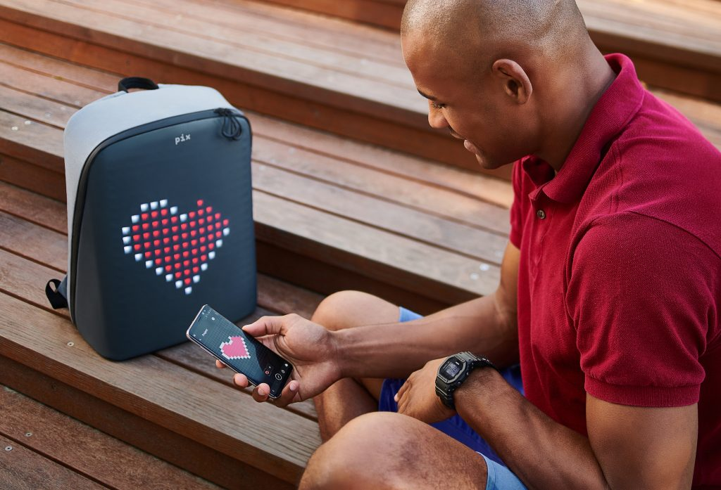 A man creates custom pixel art on his phone that can be seen on his pixel art backpack from Pix