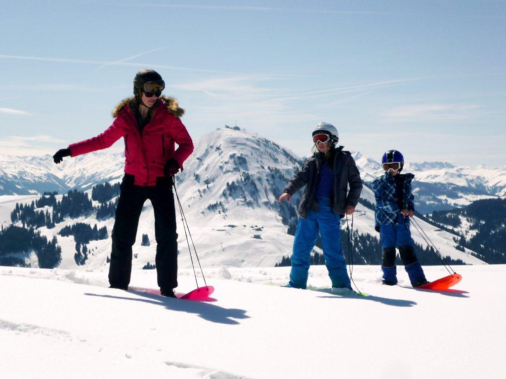 A family is seen snowboarding using Axiski's multi-terrain ski boards