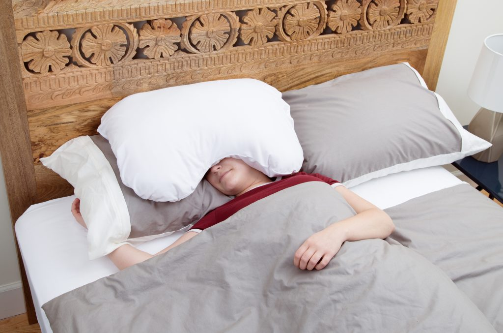 A person sleeps soundly with Sleep Crown's over-the-head relaxation pillow