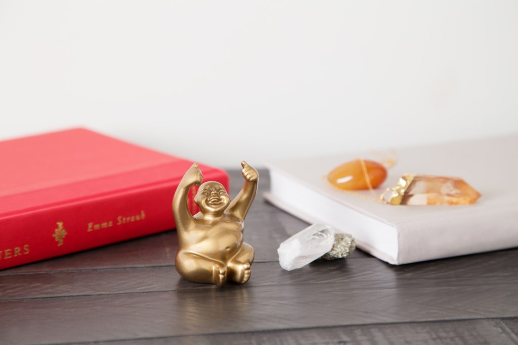 A miniature gold smiling monk figurine from Suburban Monk sits on a desk surrounded by crystals
