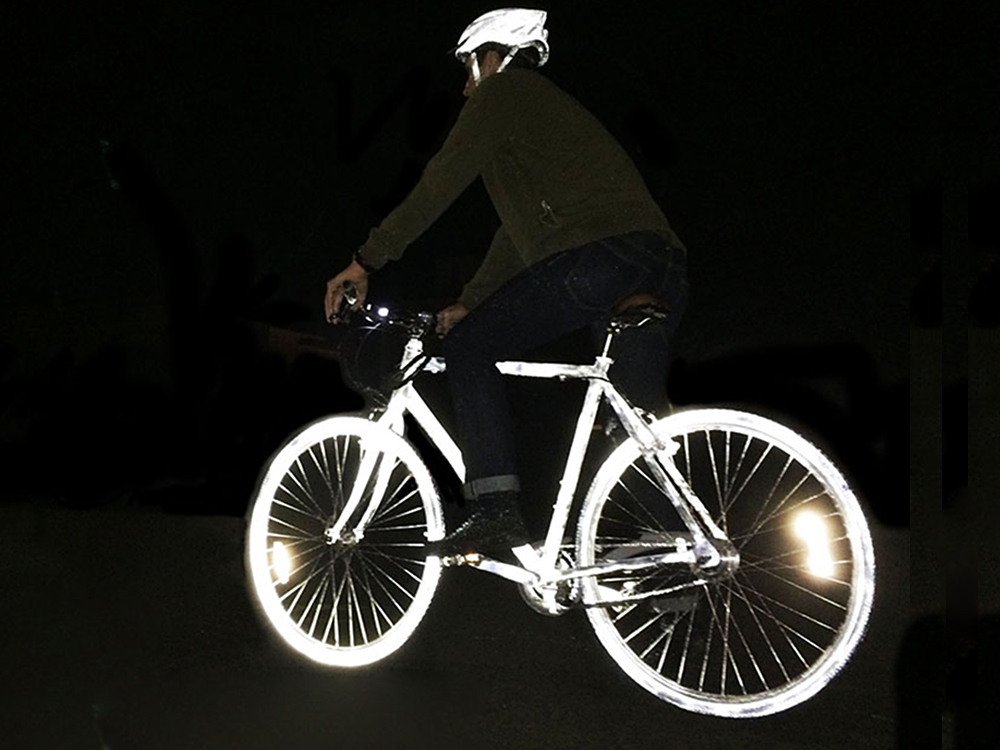 A person is seen biking at night with Albedo100 permanent reflective spray paint painting all over their bike and helmet