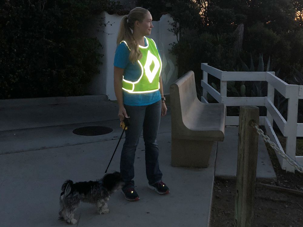 A woman is seen wearing a reflective safety vest from Arrowhere as she walks her dog at night