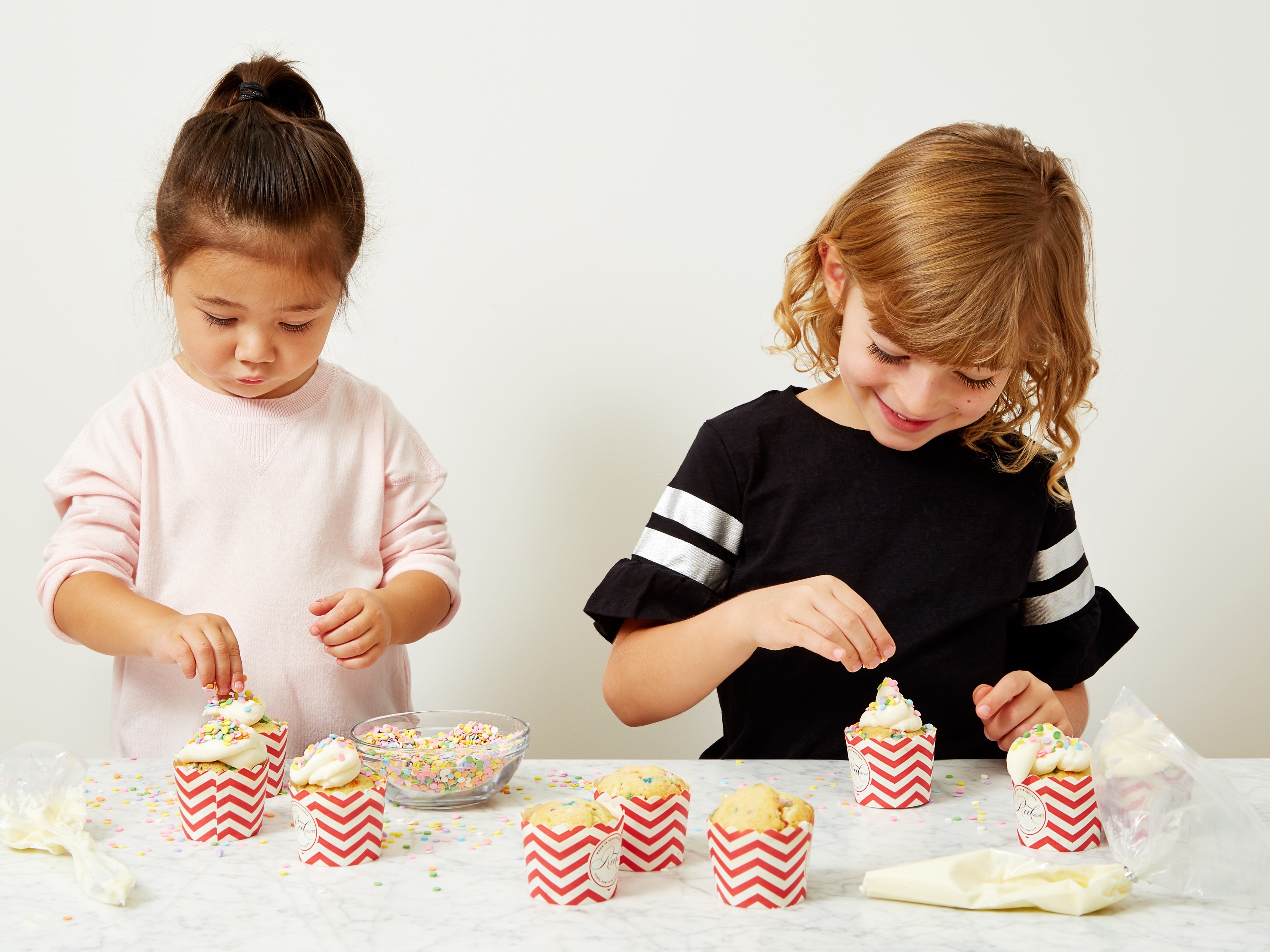 Two little girls are seen decorating cupcakes from Red Velvet NYC