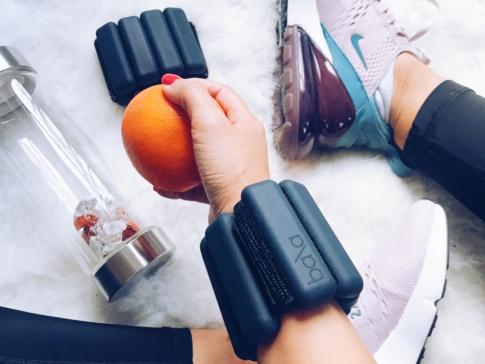 A person is seen holding an orange wearing black BALA weighted bangles