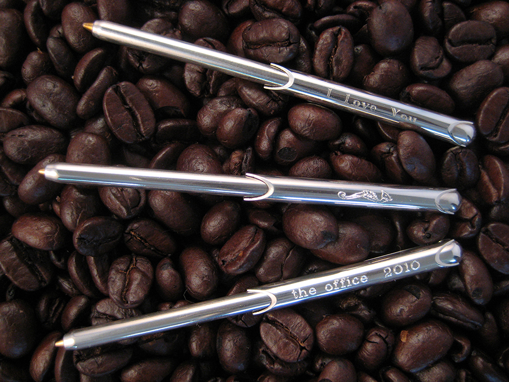 """Three engraved wallet pens lay on a bed of coffee beans. Inscribed on them are: """"I Love You"""", a seahorse outline, and """"The Office 2010"""""""