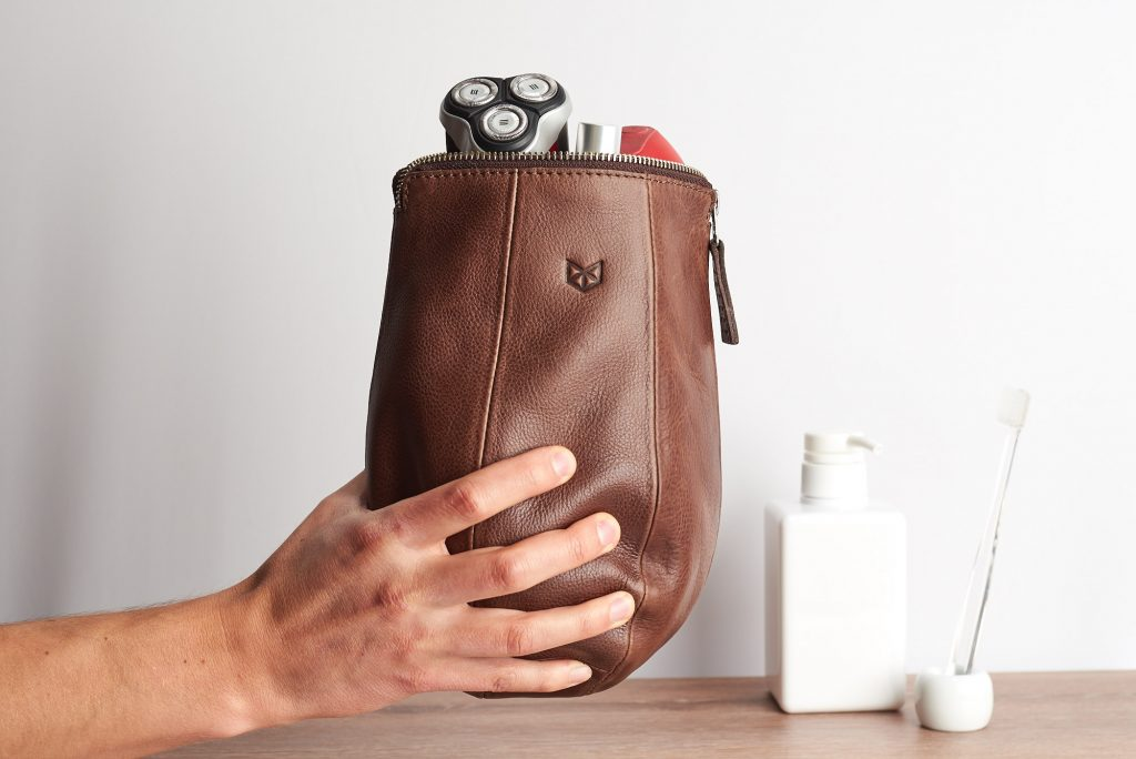 A razor and other toiletries are seen peaking out of a brown leather punching bag-styled bag from Capra Leather