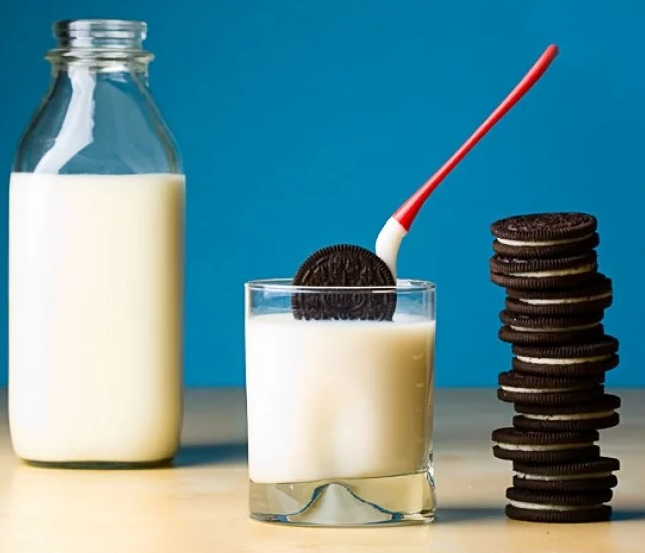 An Oreo is seen being dipped into a glass of milk using a Dipr cookie spoon