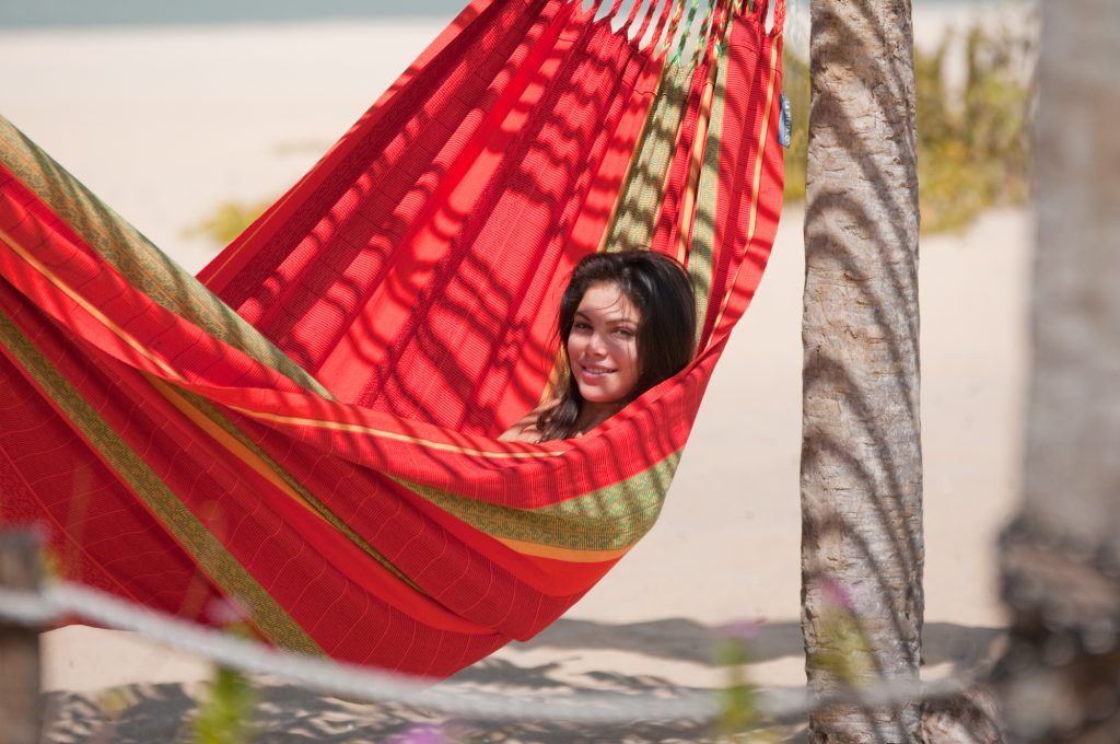 A woman is seen lounging outside in a red family hammock from La Siesta