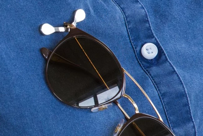 A pair of glasses is seen clipped to a shirt with a ReadeREST eyeglasses holder