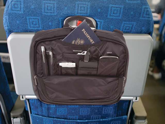 Pens, a passport and a phone can be seen in a Genius Pack high-altitude flight bag that is strapped to a plane seat's tray table