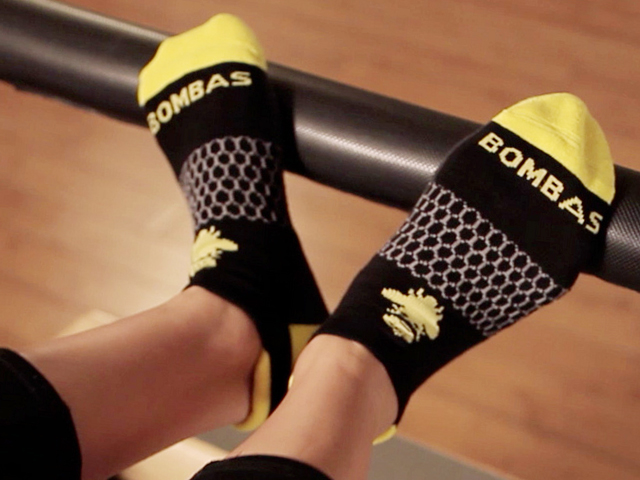 A person is seen working out wearing black & yellow Bombas ankle socks