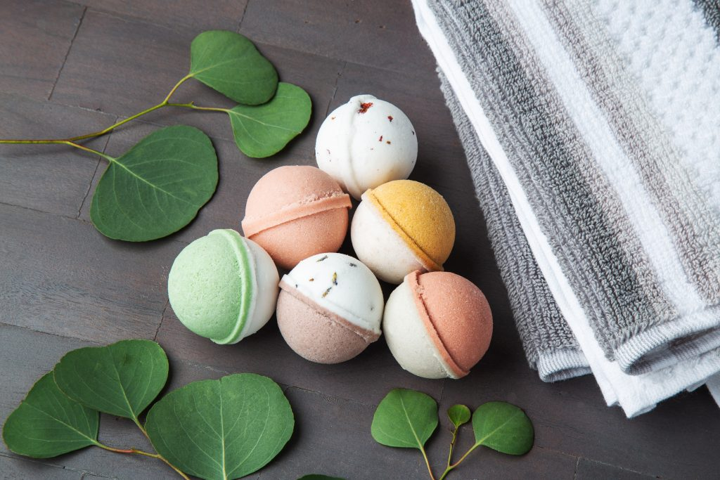 6 mini bath bombs from Level Naturals are seen on a table with awash cloth and leaves