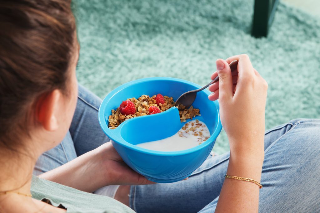 A woman is seen sitting on the floor eating a bowl of cereal in a blue OBOL anti-soggy cereal bowl