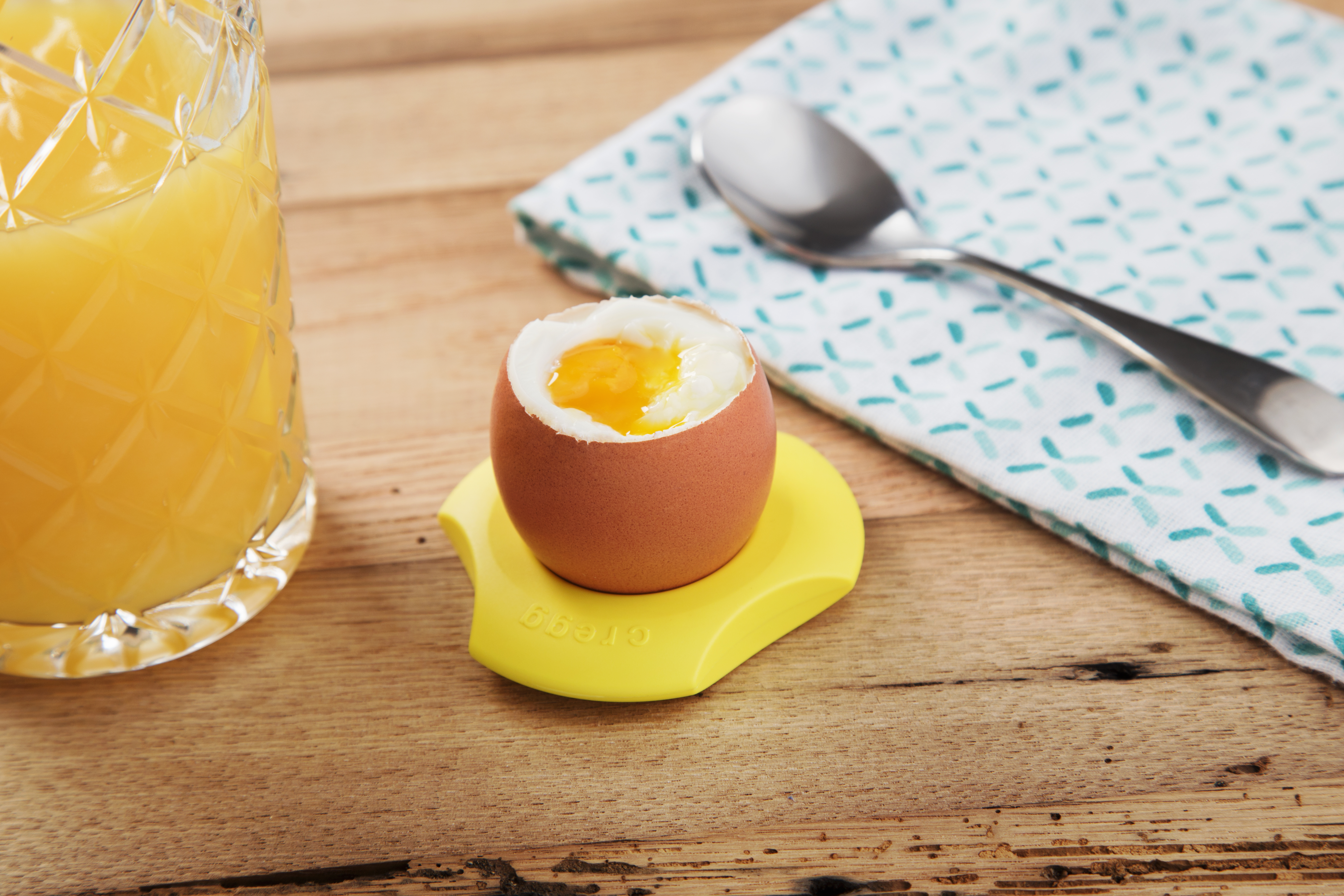 A soft boiled egg sits in a yellow Cregg egg cutter ring
