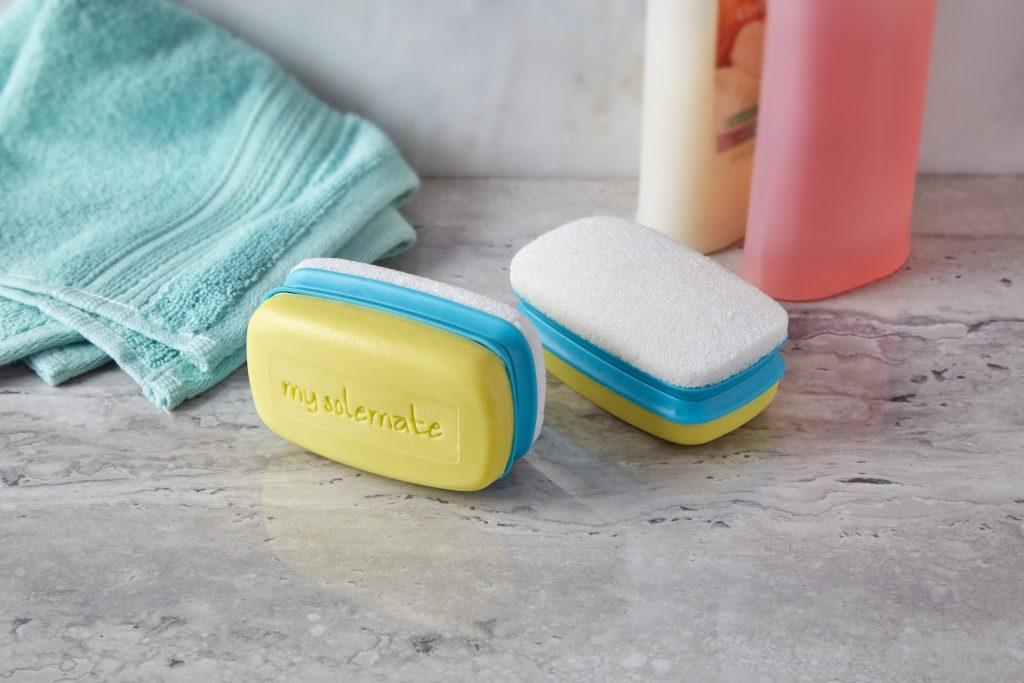 A Love, Lori My Solemate 2-in-1 foot scrubber soap is seen in a bathroom next to body wash