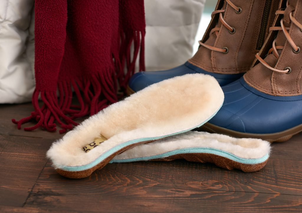 A pair of sheepskin lined cork insoles from Honey Soles sit next to a pair of boots