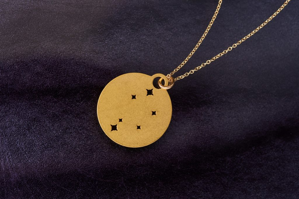 A gold Zodiac constellation necklace from Outdoor Metalworks lays on a black backdrop