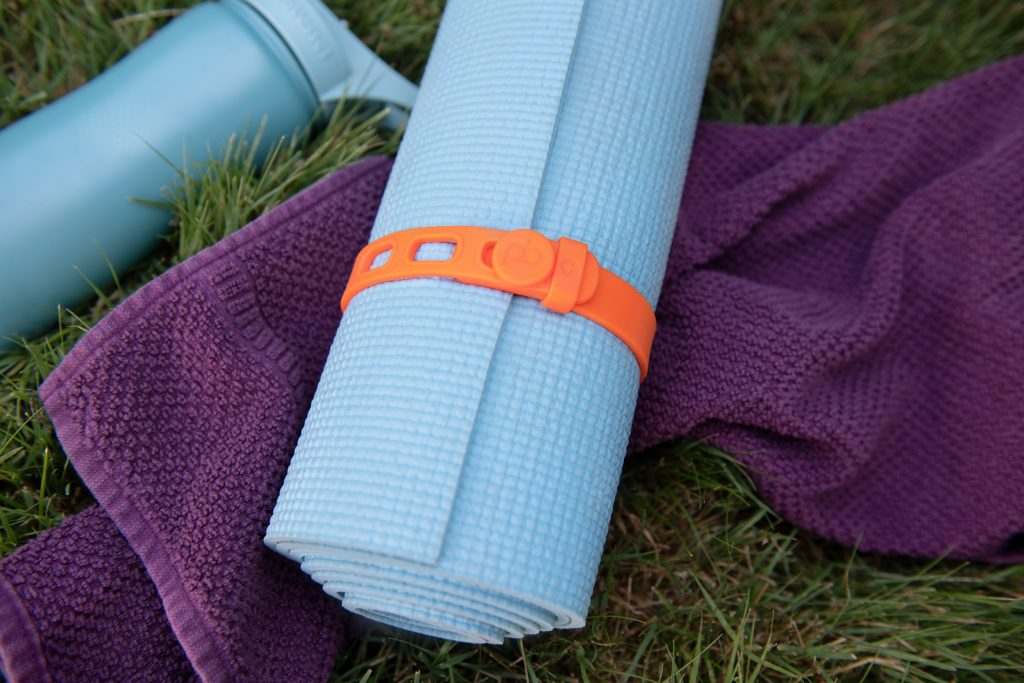 A light blue yoga mat is seen rolled up and strapped closed with an orange PackBand