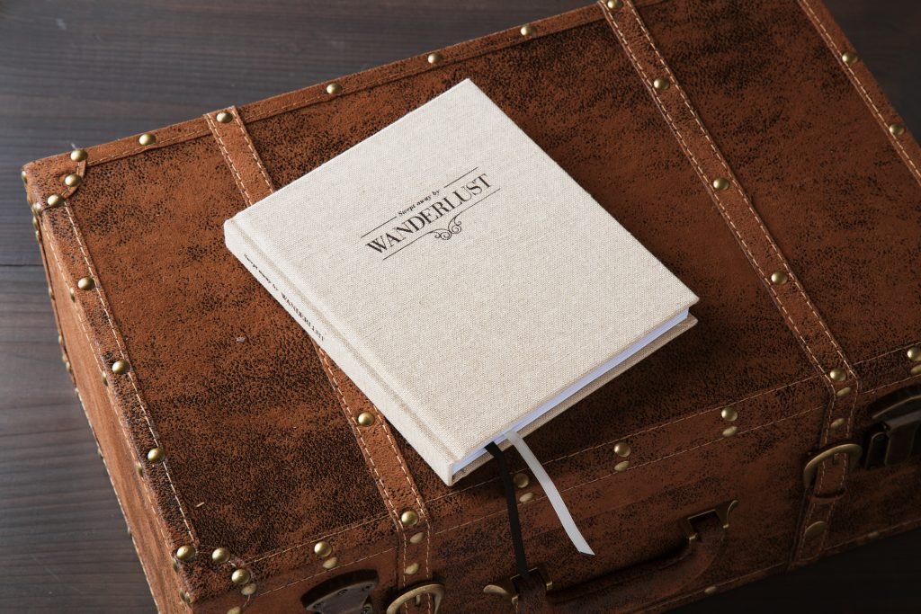 A beige Wanderlust journal from Axel & Ash sits on a trunk