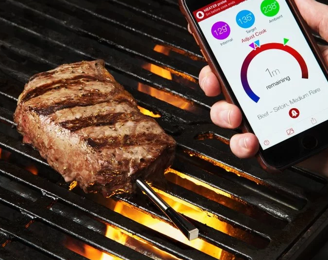 A man uses MEATER's wireless smart meat thermometer to check the temperature of his grilled steak on his phone