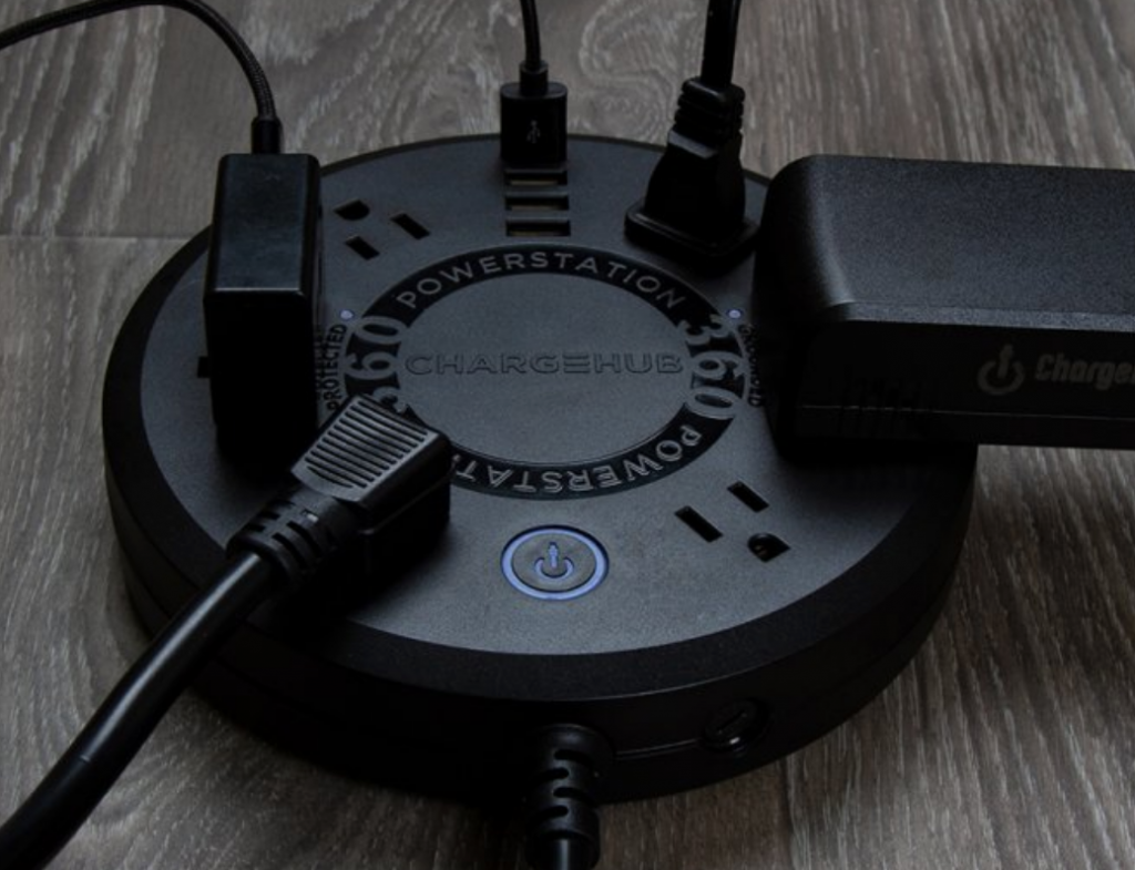 A black ChargeHub Powerstation 360 is seen charging 5 different devices