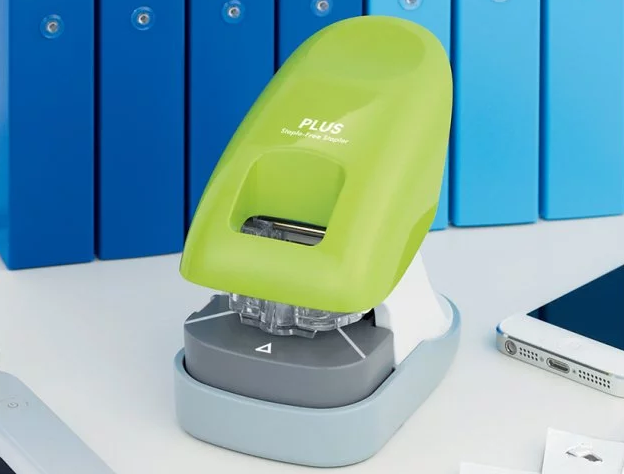 A lime green staple-free stapler from PLUS America sits on a desk