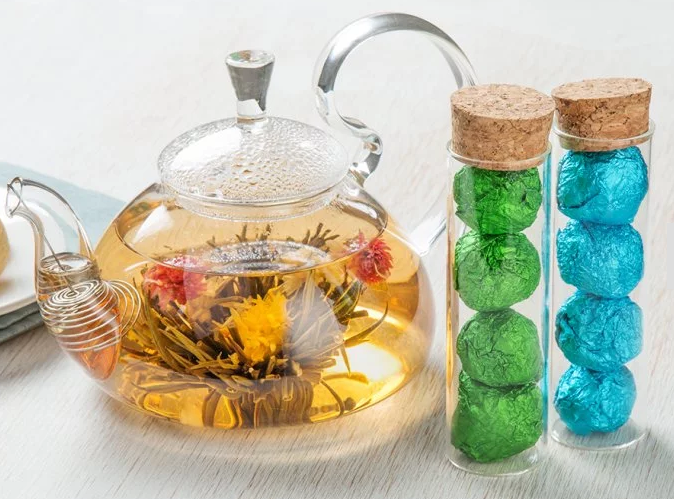 Flower tea blooms in a tisane from the Flower Pot Tea Company next to 2 canisters of blooming tea flowers