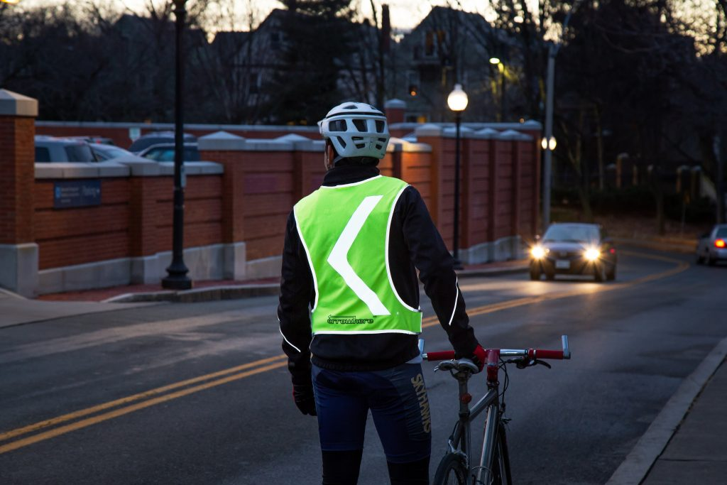 A person is seen riding their bike at night wearing an Arrowhere reflective safety vest