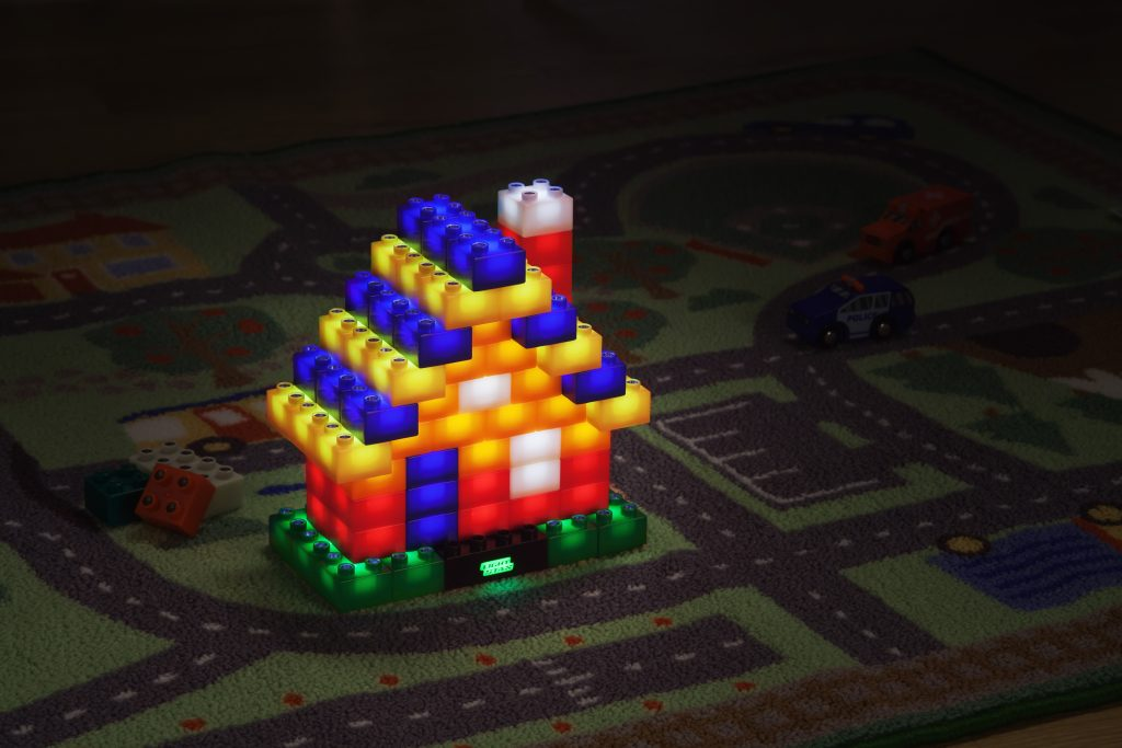 A house built from Light Stax light up building blocks is seen on a town play rug