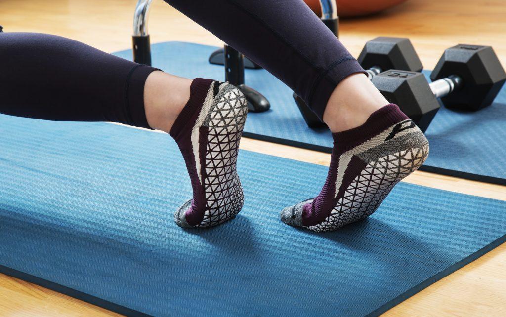 A woman is seen stretching on a mat wearing burgundy grip socks from Pedestal Footwear