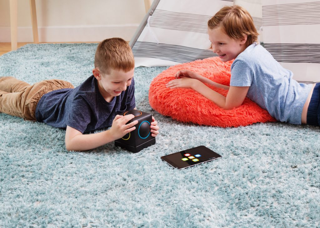 Two kids are seen lying on the floor playing with a Skoogmusic 2.0 touch & play music cube