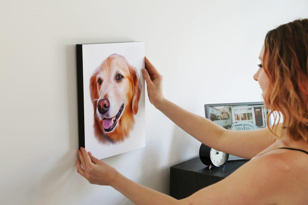 A woman is seen hanging a custom digital pet portrait of her Golden Retriever on the wall