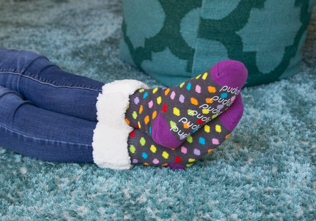 A person is seen lounging on a teal carpet wearing polka dot PUPS slipper socks