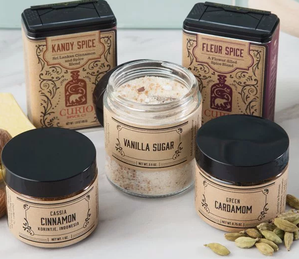 2 tins and 3 jars of baking spices from Curio Spice Co seen on a kitchen counter