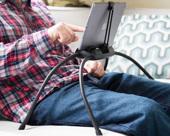 A man sits on a couch using his tablet, which rests in a Tablift tablet stand