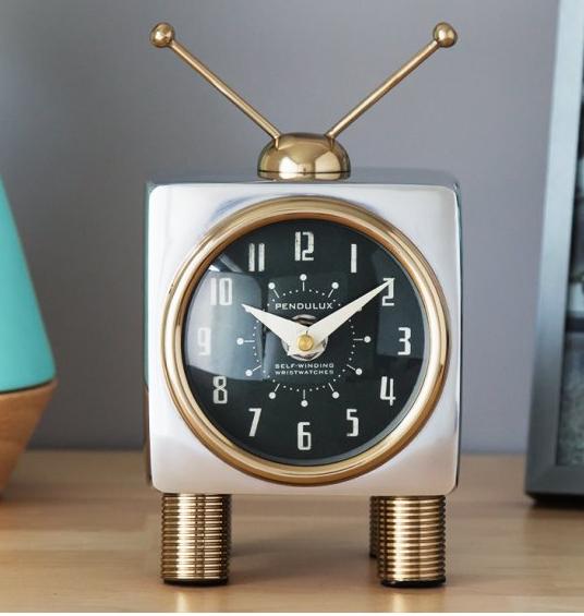 A Pendulux TeeVee table clock sits on a desk