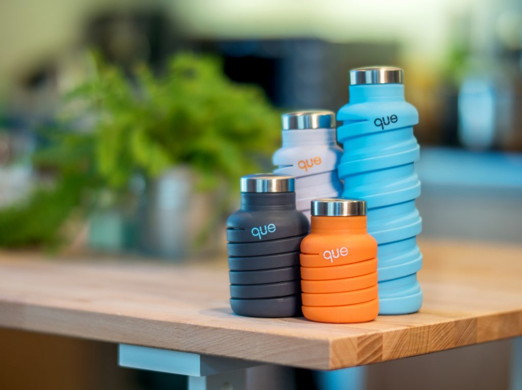 4 que collapsible silicone water bottles sit on a table