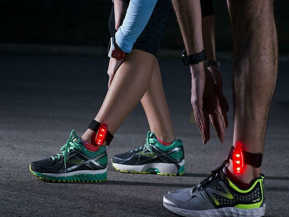 Two runners are seen wearing 4id LED lights on their ankles