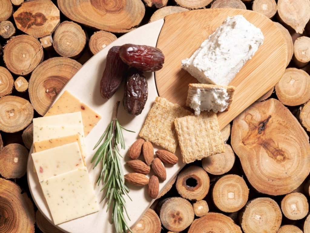 A variety of cheese, nuts and crackers sit on a bamboo cheese boards from Bamboozle Home
