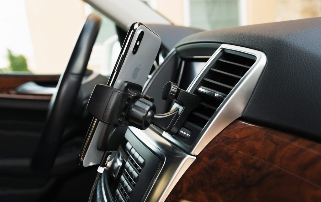 An iPhone is seen mounted to a car vent using Sqaure Jellyfish's car vent phone mount