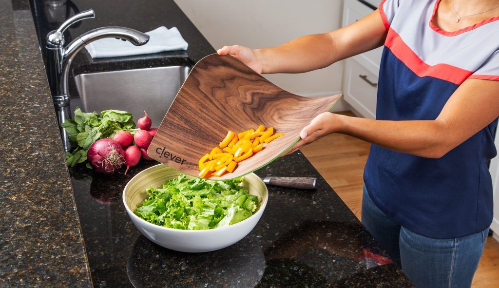 A woman is seen dumping freshly sliced yellow peppers into a salad bowl using woodNflex's flexible wooden cutting board to drop them in