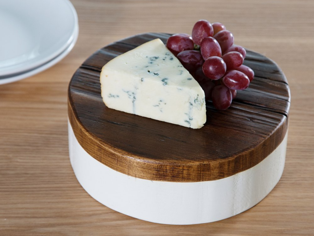A wedge of blue cheese and grapes sit on an elevated trivet from etuHOME