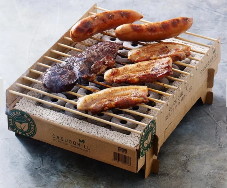 Meat is seen grilling on a Casus eco-friendly biodegradable grill