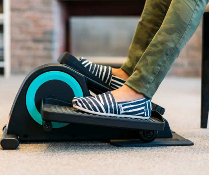 A woman wearing TOMS is seen using a Cubii under desk elliptical at work