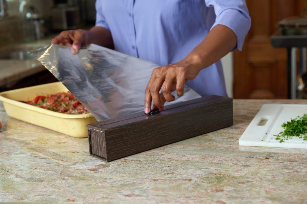 A woman is seen cutting a sheet of tinfoil using Chicwraps' woodgrain wrap dispenser