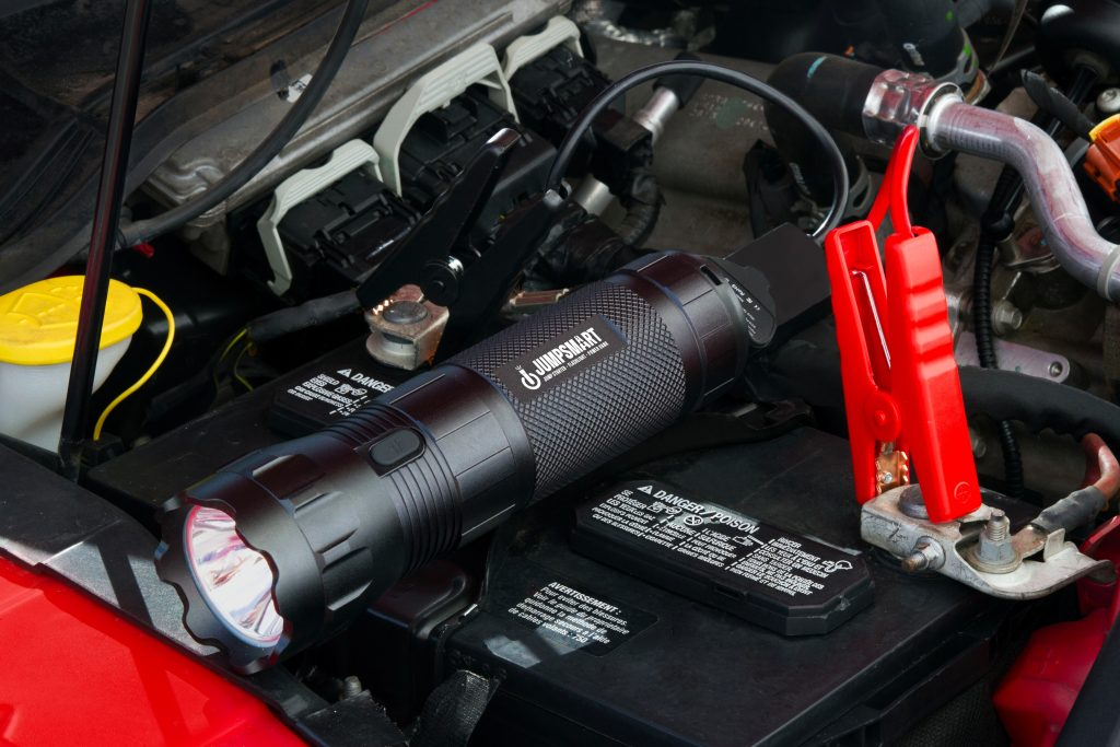 A 3-in-1 portable jump starter from JumpSmart is seen hooked up to the battery of a car